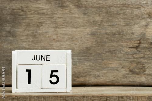 Fényképezés  White block calendar present date 15 and month June on wood background