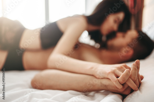 Poster Spa Sexy couple lying and kissing on big white bed