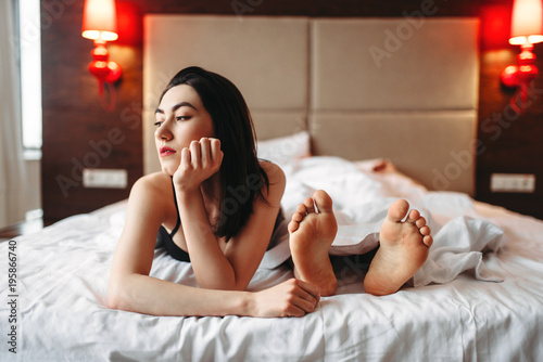 Woman in underwear lying in bed against male feet Canvas Print