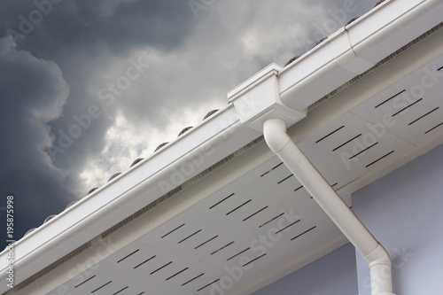 Fototapeta white plastic rain gutter and dark sky