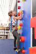 Little girl on climbing wall in entertainment center.