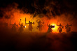 canvas print picture - Medieval battle scene with cavalry and infantry. Silhouettes of figures as separate objects, fight between warriors on dark toned foggy background. Night scene.