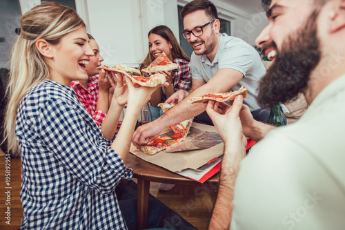 Fototapeta Group of young friends eating pizza.Home party.Fast food concept. obraz