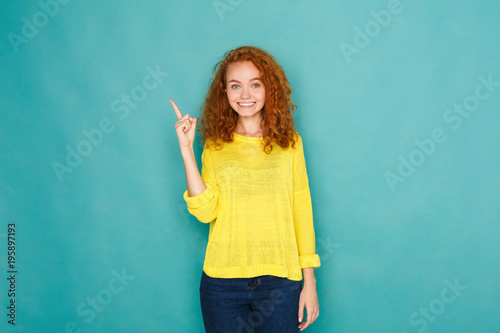 Valokuva  Attractive young woman pointing her finger up