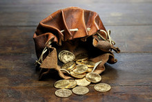 Swiss Vreneli Gold Coins In A Leather Purse On Rustic Wooden Background
