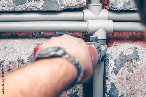 Fotografia, Obraz The worker carries out plumbing works in the house, assembles water pipes from p