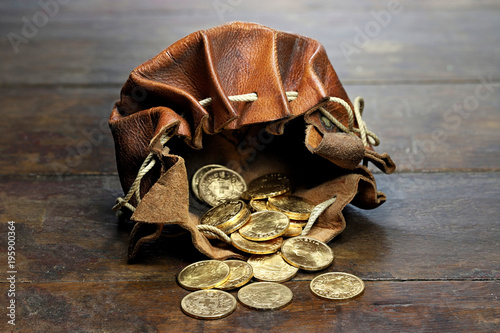 Swiss Vreneli gold coins in a leather purse on rustic wooden background Wallpaper Mural