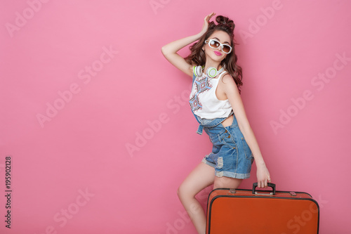 Papiers peints Magasin de musique Happy beauty woman traveler holding a vintage suitcase on road. Fashion People Lifestyle Travel concepts. Cute glamour girl in sunglasses with curly hair posing in studio.