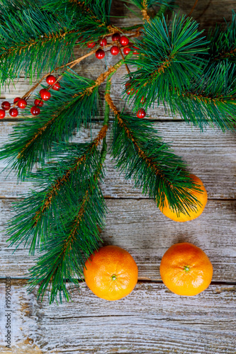 Fotografie, Obraz  Christmas concept with Tangerines, Fir branches with spices on the old rustic wooden table