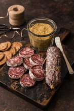 Salami And Crackers Are Topped With Mustard For A Spicy Appetizer