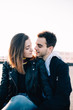 Sensual and tender portrait of young attractive and beautiful couple in 20s, hug and embrace each other passionately, kiss and cuddle outside in sunset on rooftop. Hipsters and true emotions of love