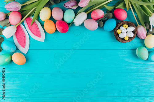 Photo  Easter composition with colored eggs, rabbit ears, nest and tulips on a blue wooden background