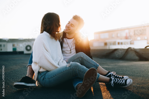 Awesome cool and attractive couple on romantic date sit on rooftop awesome cool and attractive couple on romantic date sit on rooftop at beautiful sunset light leaks hug altavistaventures Choice Image