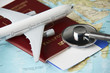 Leinwandbild Motiv Boarding pass and a passport travel documents with medical stethoscope and airplane on world map background, close-up. Medical travel concept