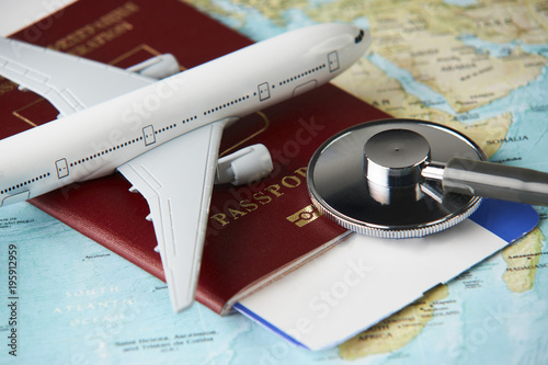 Foto  Boarding pass and a passport travel documents with medical stethoscope and airplane on world map background, close-up