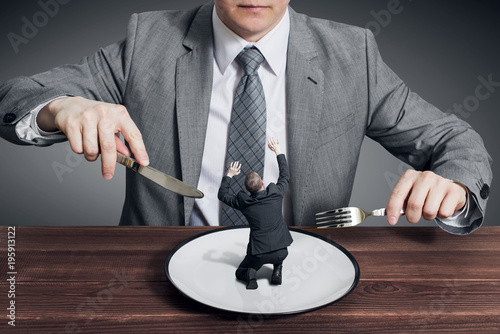 Businessman holding fork with knife and ready to eat small scared businessman on the plate Canvas Print
