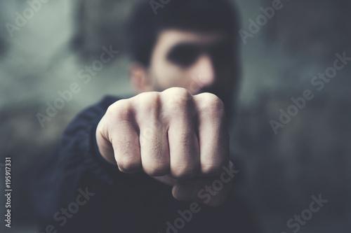 Fotografiet  man  clenched fist on dark background