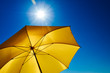 canvas print picture - Gelber Sonnenschirm mit strahlend heller Sonne und blauem Himmel