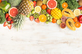 Fototapeta Fototapety do kuchni - Fruits and vegetables rich in vitamin C, oranges mango grapefruit kiwi kale pepper pineapple lemon sprouts papaya broccoli, on wooden white table, top view, copy space, selective focus