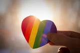 Fototapeta Tęcza - LGBT day concept,  hand holds a heart painted like a LGBT flag, silhouetted against sun