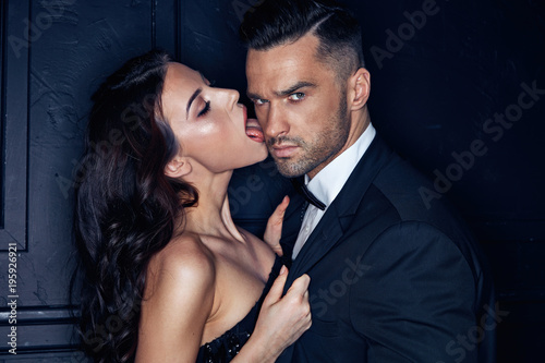 Sensual young woman licking her handsome, elegant lover