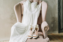 Close-up Of Wedding Shoes On A Pink Armchair Next To A Wedding Dress Against A Gray Concrete Wall