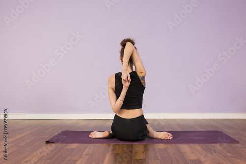 Fototapety, obrazy: Beautiful Young woman practicing yoga indoors. Wearing black sportswear. Using purple mat. Wood floor and violet background. Sports and lifestyle