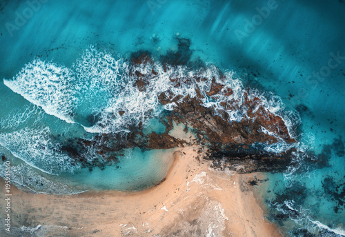 Aerial view of waves, rocks and transparent sea. Summer seascape with ocean, sandy beach, beautiful waves, cliffs, blue water at sunset. Top view from drone. Rocky coastline. Travel. Maldives. Concept