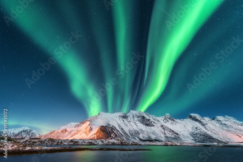 Foto auf Gartenposter Nordlicht Aurora borealis. Lofoten islands, Norway. Aurora. Green northern lights. Starry sky with polar lights. Night winter landscape with aurora, sea with sky reflection and snowy mountains.Nature background