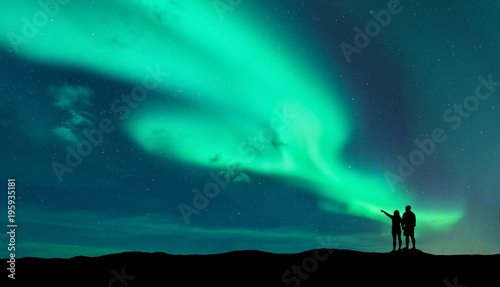 Poster Aurore polaire Aurora borealis and silhouette of standing man and woman who pointing finger on northern lights. Lofoten islands,Norway. Aurora. Sky with stars and polar lights. Night landscape with aurora and couple