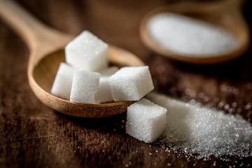 Close up the sugar cubes and cane in wooden spoon on the table