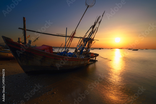 Fotobehang Rood Fishing boat in on the beach at sunset.