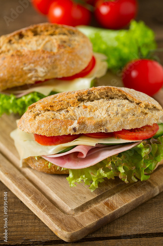 Staande foto Snack Wholegrain Ciabatta Sandwich with Lettuce, Tomatoes, Ham and Cheese
