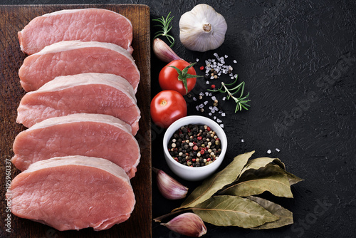 Raw sliced pork loin with tomato, pepper, rosemary, bay leaf and garlic on a dark background. Fresh meat.