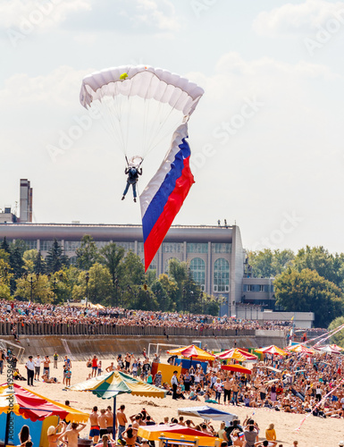 Poster Luchtsport Russia, Samara, August 22, 2015: air show on the Volga embankment, the paratrooper lands on the beach, with the Russian flag on a summer sunny day