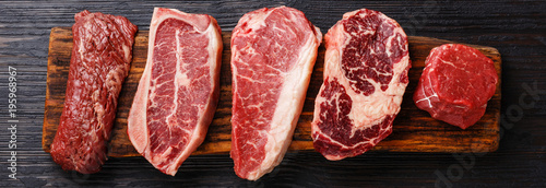 Photo Stands Meat Variety of Raw Black Angus Prime meat steaks Machete, Blade on bone, Striploin, Rib eye, Tenderloin fillet mignon on wooden board