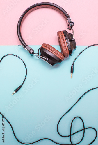 Fancy headphones laying on a flat pink and blue surface. Analog wire frames the layout.