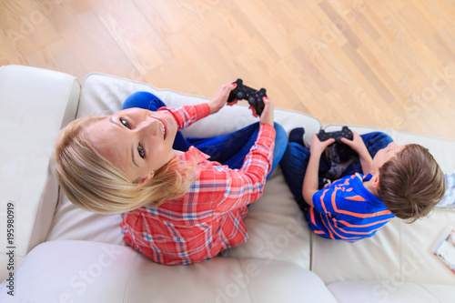 Aluminium Prints Magic world Mother and son playing video games on console