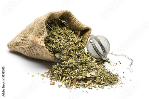 Photo  green tea mixture in juta bag with infuser on white background