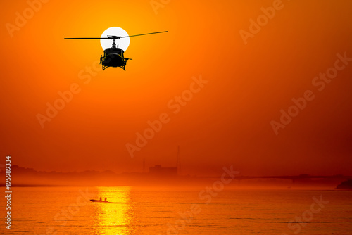 Türaufkleber Hubschrauber silhouette of helicopter with sunset.