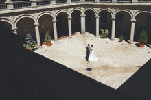 Bride And Groom Looking Each Other In A Courtyard