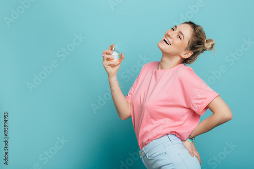 Fototapeta young positive woman holding a perfume bottle and applying it, while standing against blue background. applying fragrance obraz