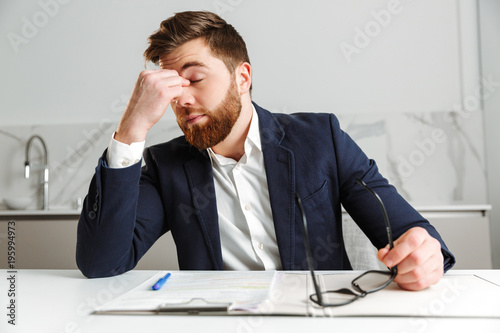 Photo Portrait of a tired young businessman dressed in suit