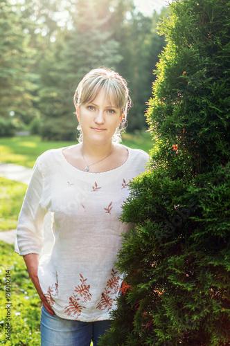 Fotografie, Obraz  Blonde girl in a white sweater strolls in the park