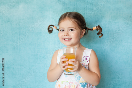 Fotografia, Obraz  Smiling girl with funny pigtails with glass of juice