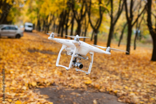 Dron with a video camera in the autumn park