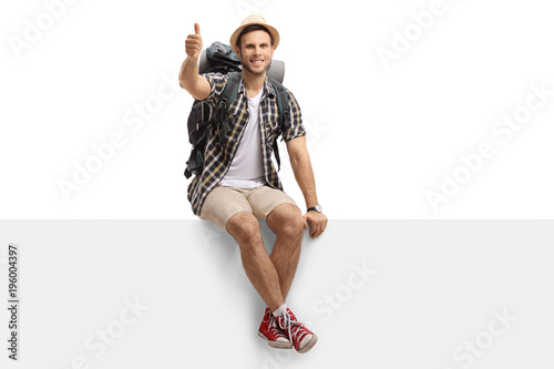 Tourist sitting on a panel and making a thumb up gesture Fotobehang