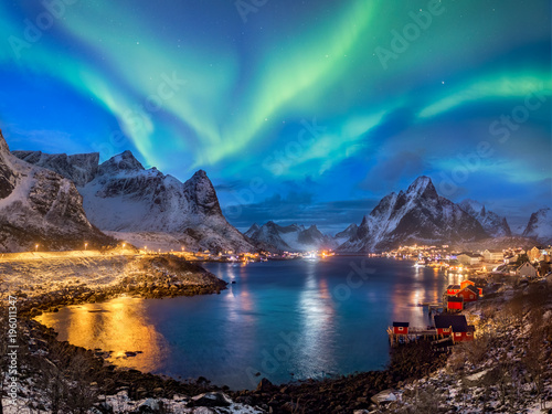 Aurore polaire wide angle panorama of reine fishing village with beautiful northern lights on a blue sky, reflections in the water and illuminated town