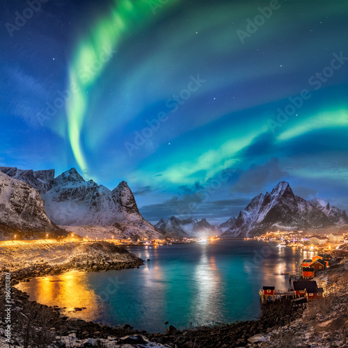 Foto op Aluminium Nachtblauw surreal green glowing northern lights over illuminated fishing village of reine lofoten islands
