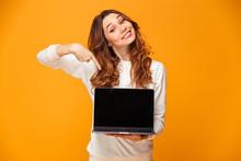 Pleased Brunette Woman In Sweater Showing Blank Laptop Computer Screen